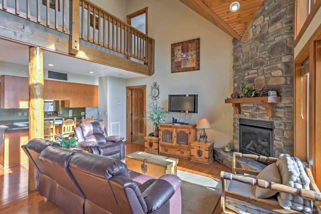 The open living area offers a gas fireplace, plush couches, and a cable TV.