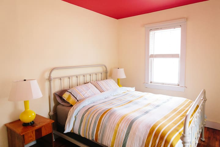 Spacious bedroom with brand new Leesa Queen-sized mattress on vintage metal bed with yellow lamps + handcrafted nightstands, blackout curtains, and a tall dresser.