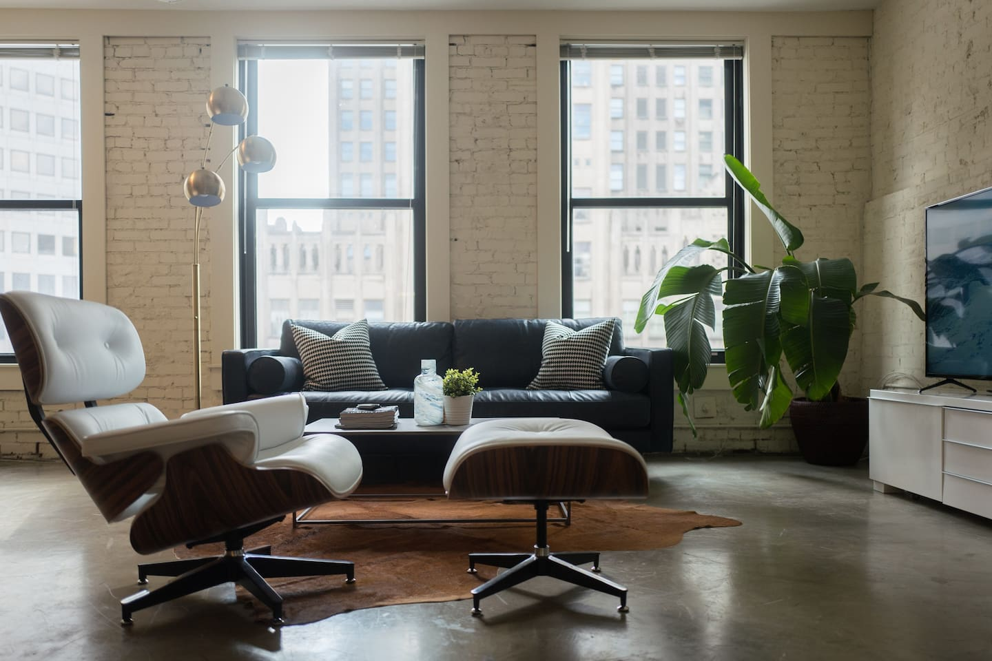 """A beautiful well-lit living room with an Eames Chair and 60"""" 40K tv."""