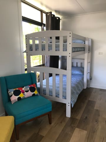 A third bedroom with single bunk beds, wardrobe and two colourful occasional chairs. This room has an oscillating wall fan.