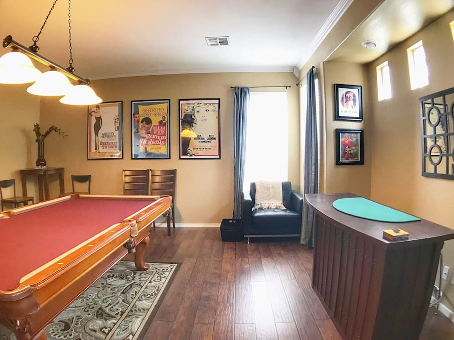Game room with pool table, bar, and lounge seating.