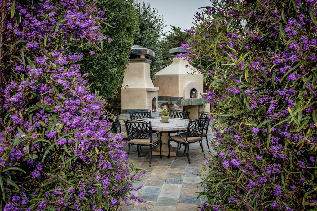 Lush gardens surround the private side patio with   a fire place and brick oven.