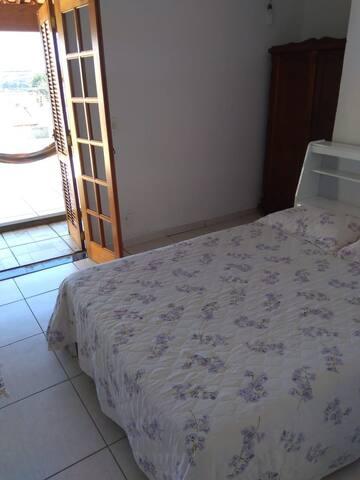 Quarto com cama de casal e porta balcão com varanda