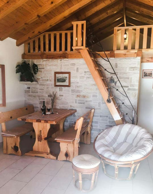 Wooden dining table, stone wall and  wooden armchair