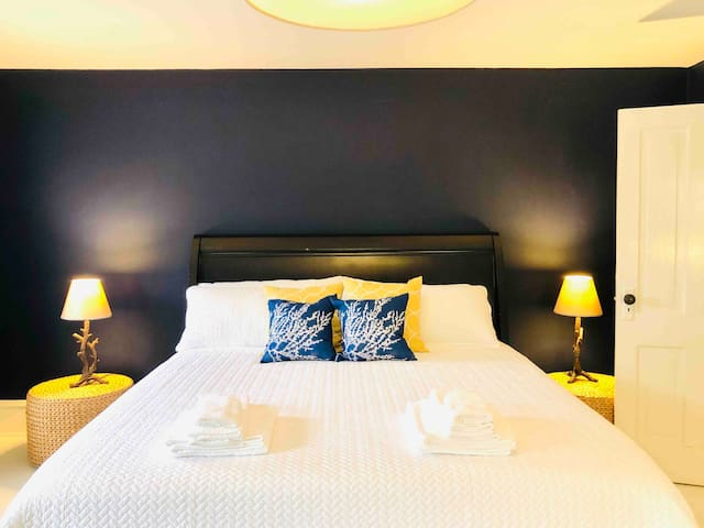 Bedroom 1 is the largest bedroom and is located on the front of the house. It's decorated in a crisp navy and white palette perfect for a beachside getaway. A gel foam California king mattress and black out drapes ensure you'll wake refreshed!