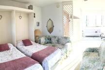 """2 couchages dans le salon et vous pouvez voir """"le coin cosy"""" dans le fond de la pièce qui se ferment avec des rideaux pour preserver l'intimité."""