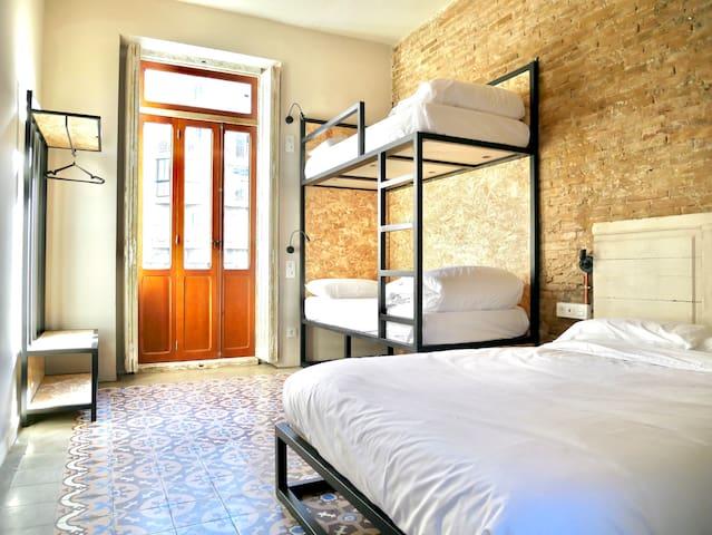 Nuestra habitación Cuádruple cuenta con una cama doble y una litera con dos camas individuales.  Hemos conservado todas esas cosas que hacen única y especial a la casa. Pared con la piedra vista y los suelos hidraulicos tan típicos de España.