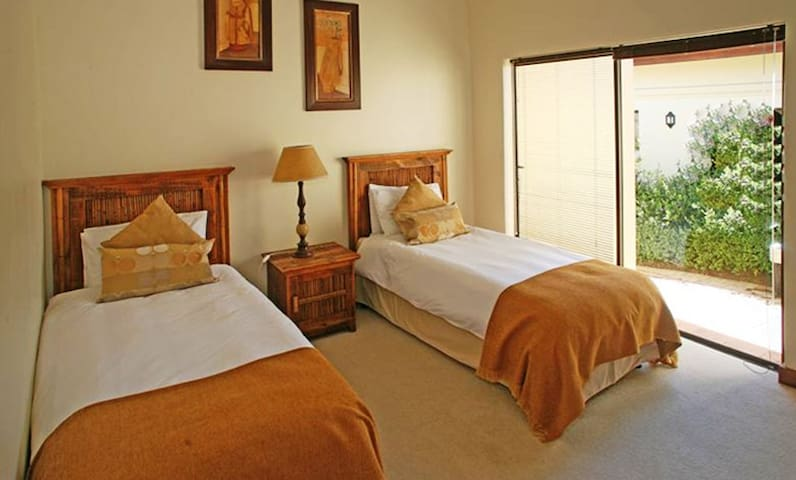 This is the middle bedroom 2, with two single beds and an ensuite bathroom including shower, basin and toilet