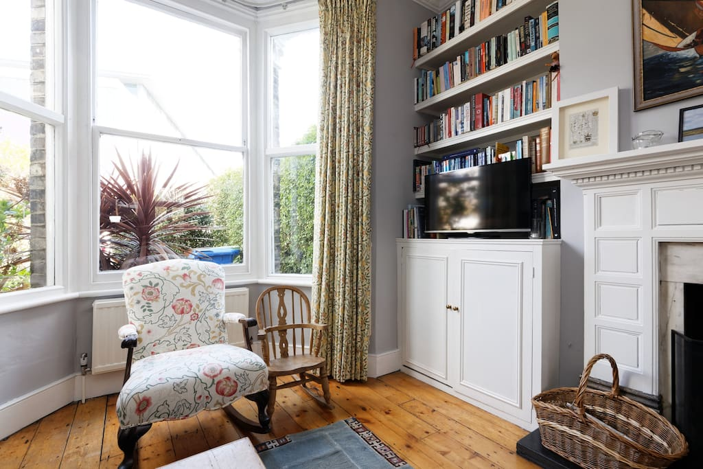 Large, bright sitting room with high ceilings, a working fireplace and a piano