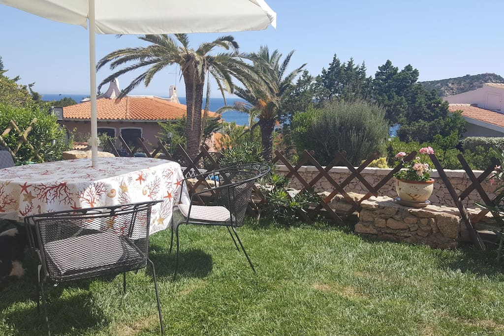 Giardino attrezzato, tavolo con sedie in ferro, divani con cuscini, ombrellone. 200 metri dalla bianca sabbia della baia. Garden furnished with table and chairs in iron, sofà with big pillows and an umbrella. Great overview over the Baja Sardinia  bay, 200 meters from the white sand beach.