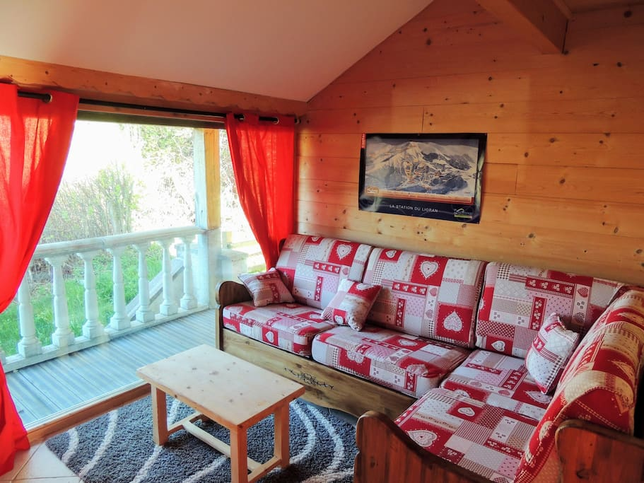 Salon chaleureux équipé d'une grande TV/écran plat, canapé convertible en un grand lit double.