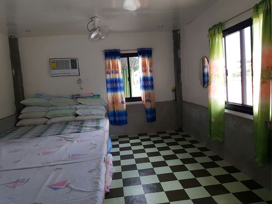 Large guesthouse bedroom with 3 king size beds, extra foam beds, AC, TV, fans
