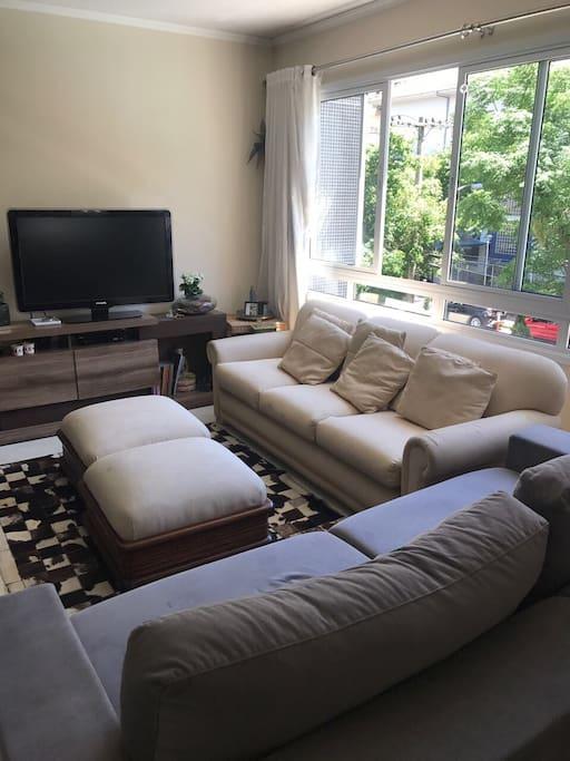 Sala de estar ampla, com sofás e televisão à cabo