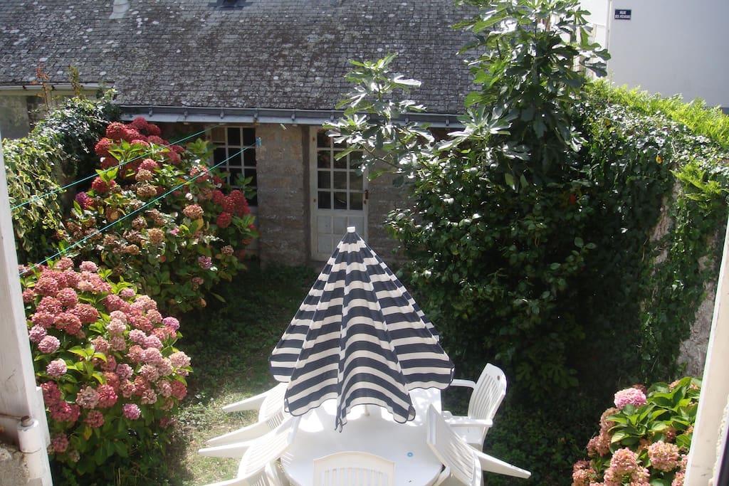 Petit jardin abrité, et au fond local avec douche retour de plage, toilette et lave linge.