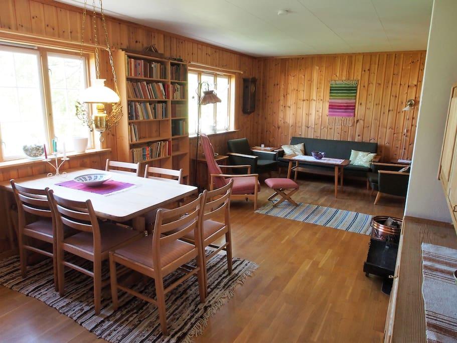 Stue med spisebord, lesestol og sofakrok.