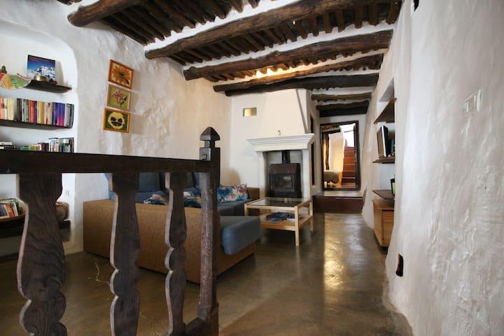 Planta de arriba con su estufa de leña y con un salón separado en dos espacios detrás el baño completo y el segundo dormitorio .