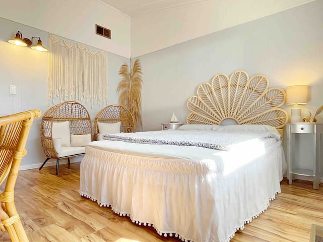 BR 3: Boho Coastal-themed room. Full-size bed with a pretty rattan petal headboard. Perfect for kids and teens with two rattan kid's egg chairs! This room has a desk with an Anthropologie rattan chair. full-sized mirror, small closet, luggage rack.