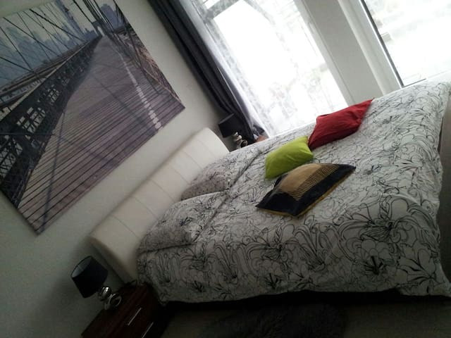 King size bed in a room separated from the living room.