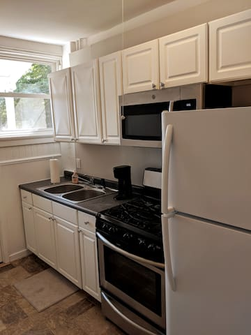 Kitchen with coffee maker, fridge, microwave, stove, essentials