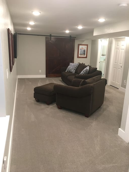 Private living room with a Smart TV, new comfortable couch and over-sized chair and ottoman and plenty of space for an air mattress (available upon request)