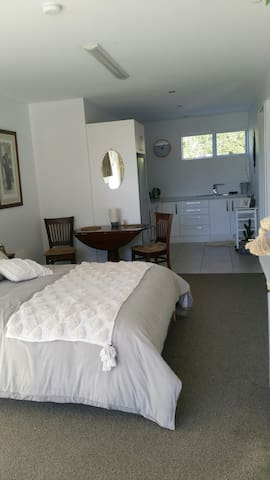 A spacious open plan room beautifully decorated and with a place to sit, a dining table to eat at, a comfortable new queen size bed and a new smart TV .