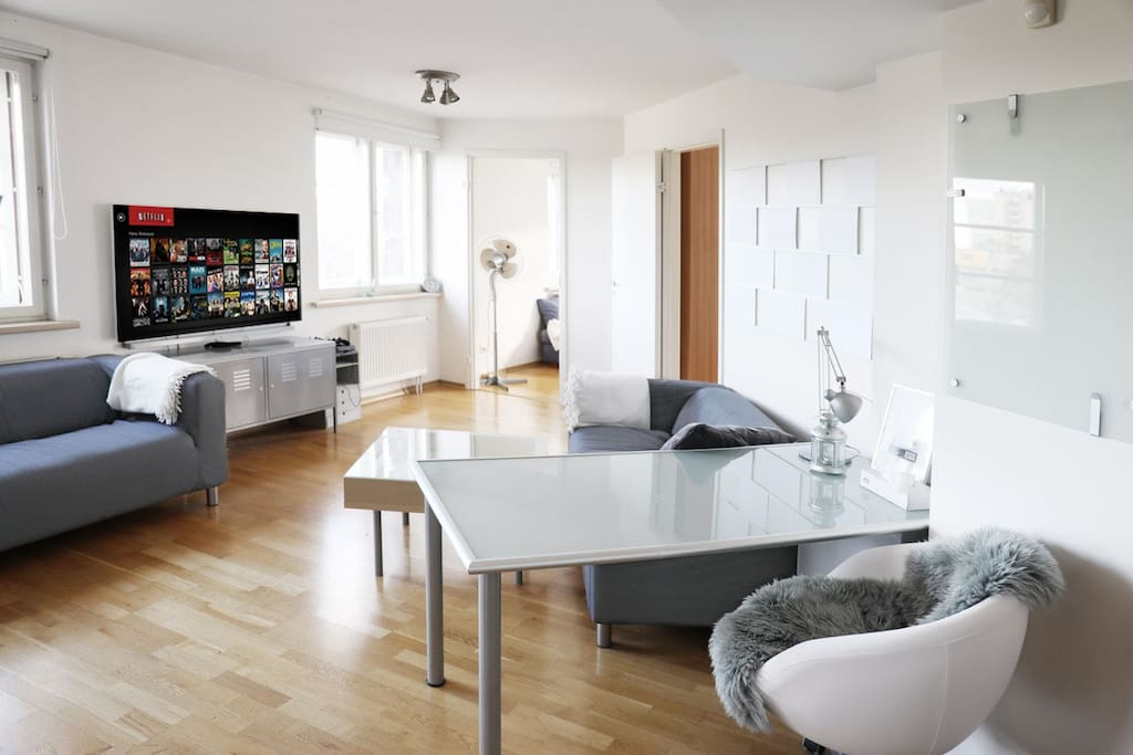 """The main room features a wide work/eating table, comfortable sofas and a 55"""" LG Smart TV along with PlayStation 4 and Netflix."""