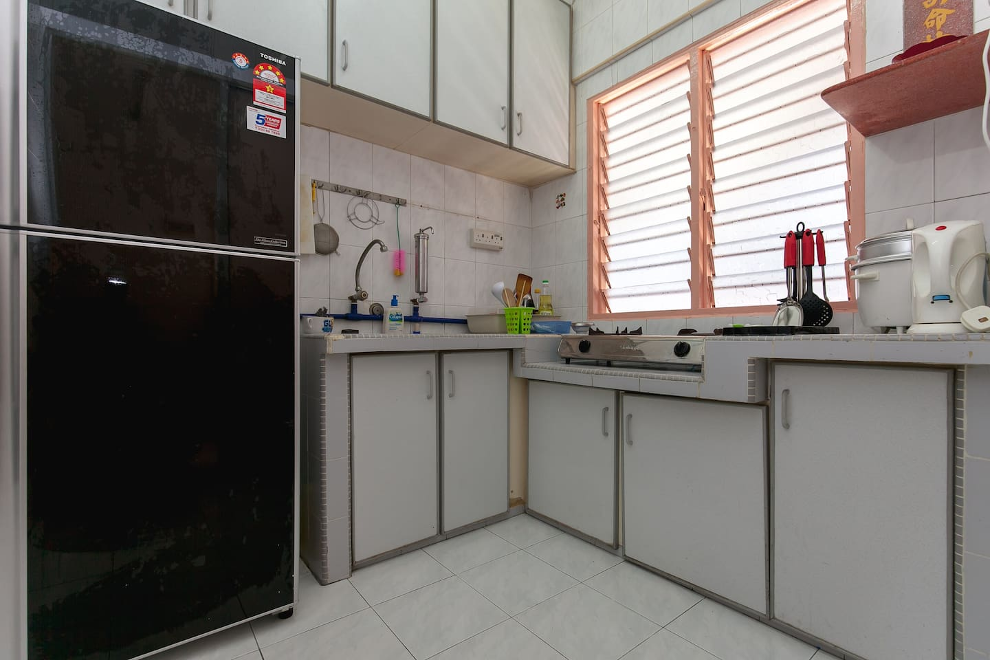 Fully equipped kitchen with kettle, gas stove, fridge, and kitchen utensils