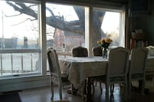 The table sits in front of three beautiful windows with a view of the old barn.