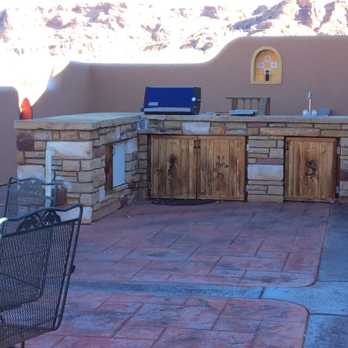 This is your private awesome outdoor kitchen area with built in BBQ, burner, sink and mini fridge.  Alcove lights come on at night.  It's pretty cool.  2 tables and outdoor seating for 8.  Plus rocking bench seat.