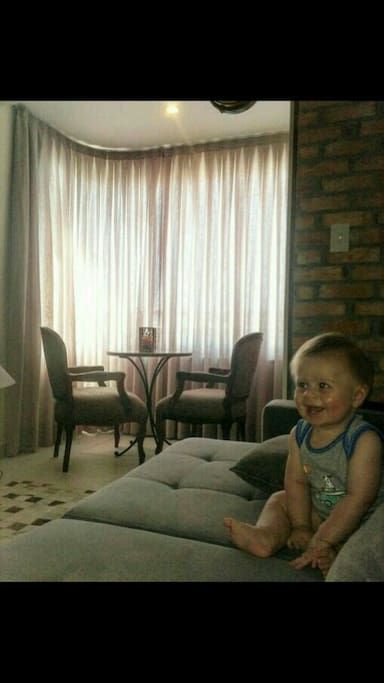 Ambiente da sala, integrada com varanda (fechamento com sistema reike). O lindão na foto é o Pedro, nosso filho.