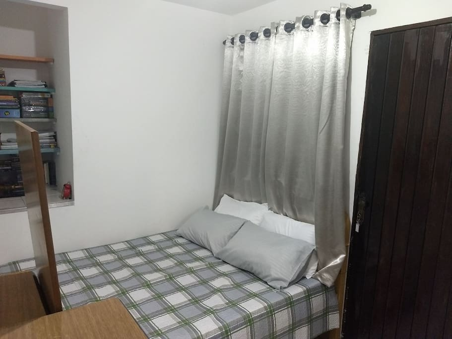 Vista da cama de casal, quarto espaçoso e bem iluminado.