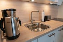 Küche mit Wasserkocher, Kaffeemaschine, Toaster, Herd, Kühlschrank, Geschirrspüler und Backofen. Geschirr, Besteck, Töpfe und Gläser sind vorhanden.
