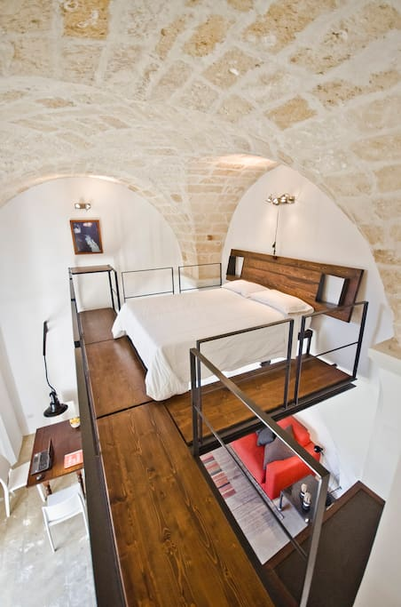 An architect's dream - the open sleeping loft has a quality queen-sized bed for restful nights and gazing up at the ancient stone arches.