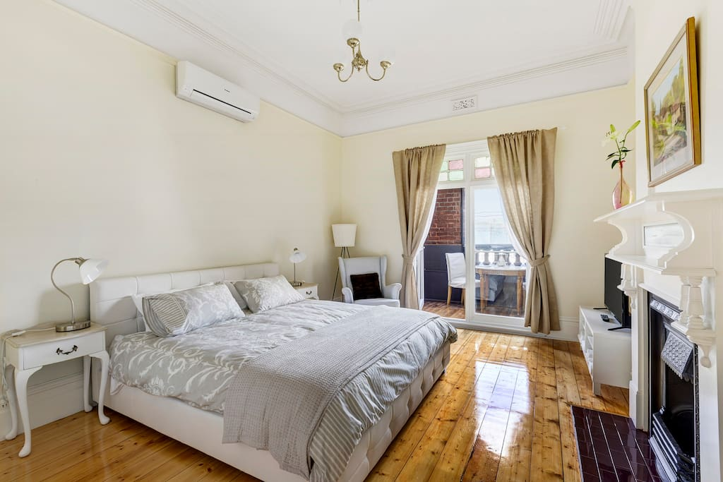 Room #2 huge room with comfy king bed, TV, lovely balcony overlooking Sydney Road, your own heating and air conditioning and a convenient cupboard for clothes with ironing board and iron.