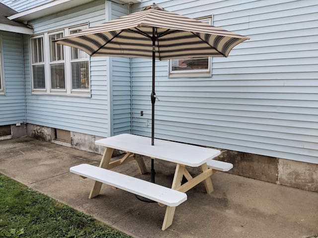 Nice outside patio seating area with large picnic table and umbrella.