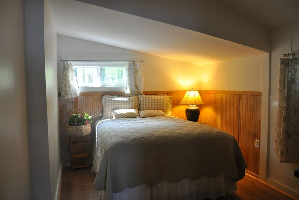 BR with queen bed and view of surrounding trees.