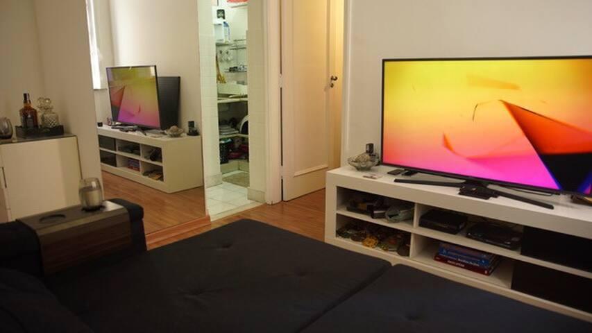Visão da sala com a cozinha à frente e a porta do quarto.
