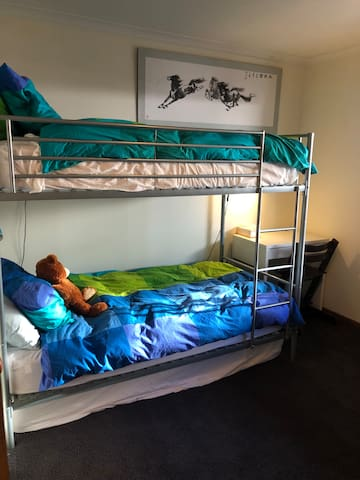 Kids' bunk room, complete with desk and a cupboard full of games and books. Quality mattresses, comfy pillows and warm feather doonas.