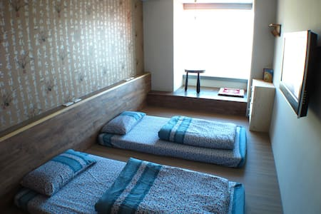 Two single beds with a Japanese Style Floor, flatscreen TV.