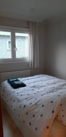 Slaapkamer met 2 persoonsbed en een grote kast met opbergmogelijkheden.
