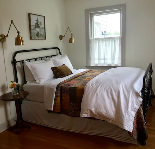 Main floor bedroom with queen-size iron bed, crisp white linens and patchwork quilt.
