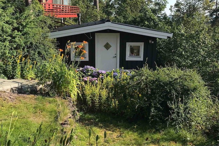 Small cabin in a quiet garden, view of the Fjord .