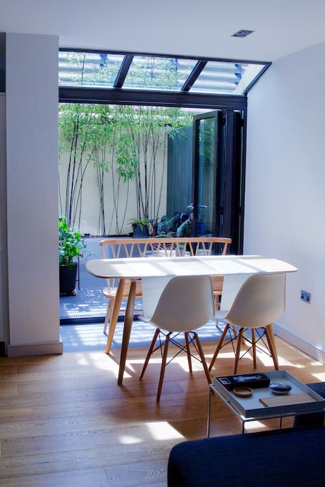 The light-filled dining area with Ercol dining table and mid-century chairs. There are bi-folding doors that open onto the sunny private courtyard