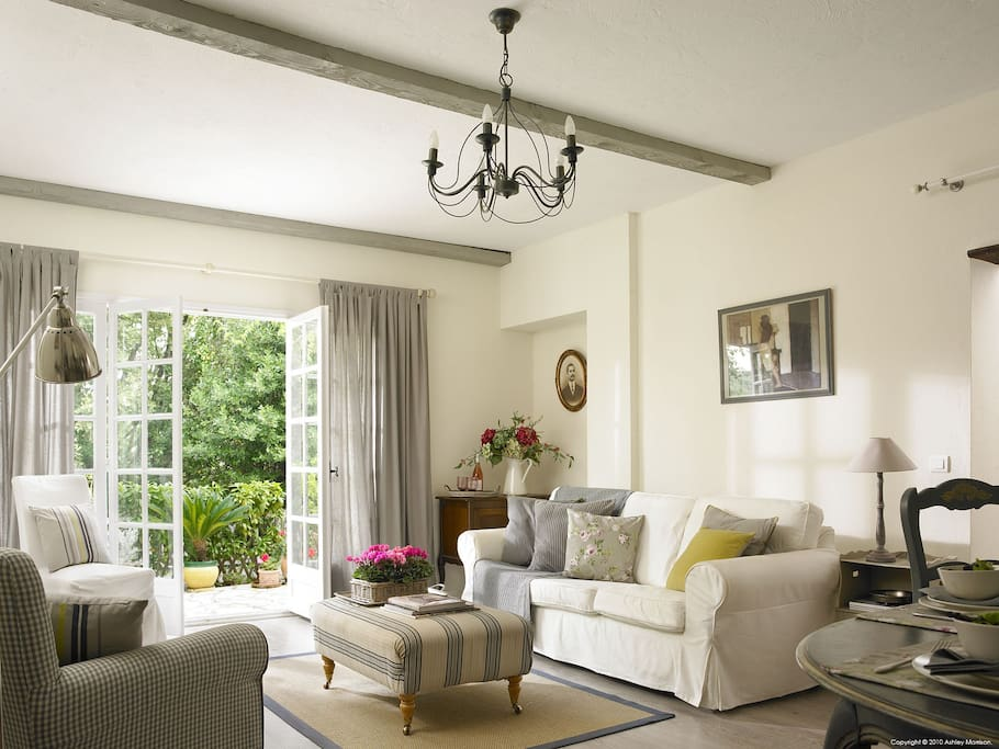 Spacious living room with French doors leading to a courtyard garden with woodland beyond. In May the villa is flooded with the smell of Jasmin....