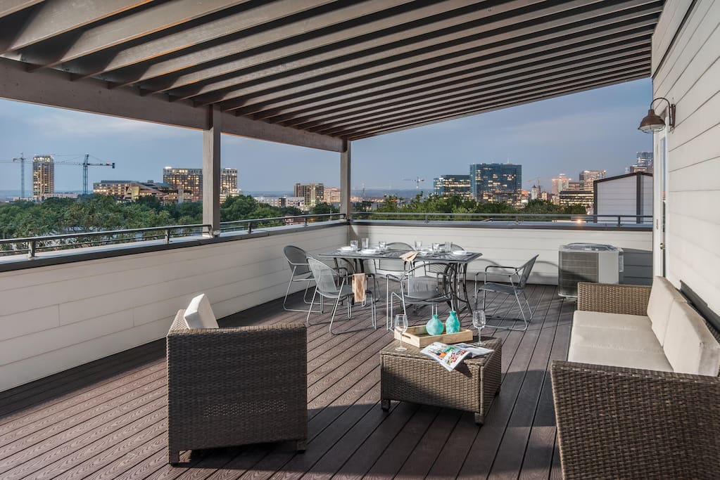 The covered rooftop deck boasts comfortable lounge furniture and a 6-seat patio table.