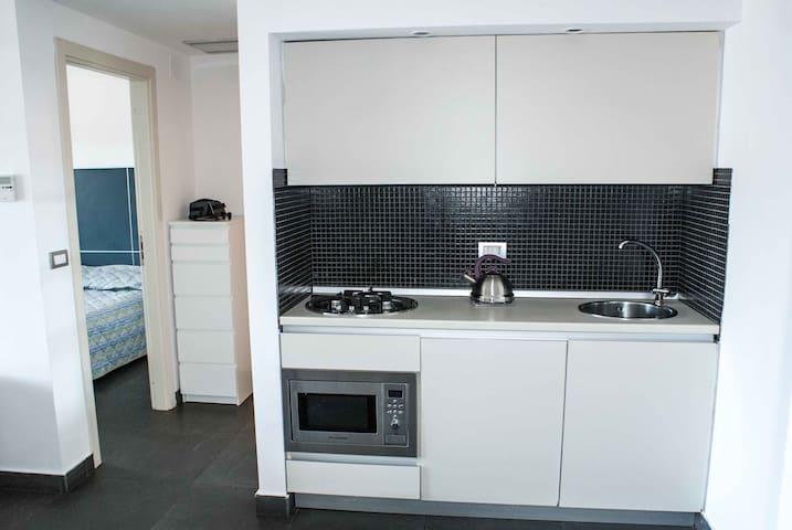 cucina con fornelli, forno e vista su camera