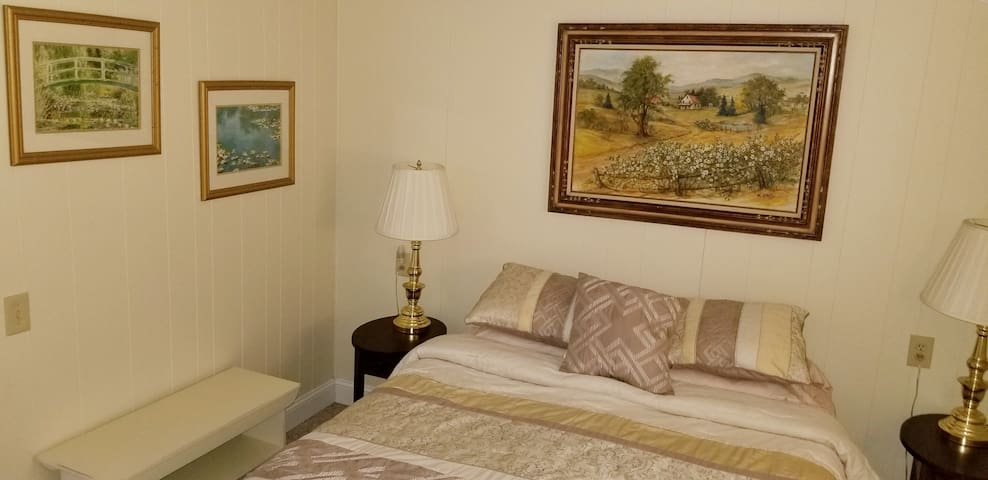 The master bedroom includes two lamps and a queen sized bed.