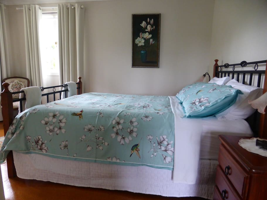 Bedroom 1 with views of the pool, gardens & Mt Zahl