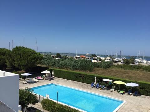 Apartmán u moře: bazén, pláž a přístav.