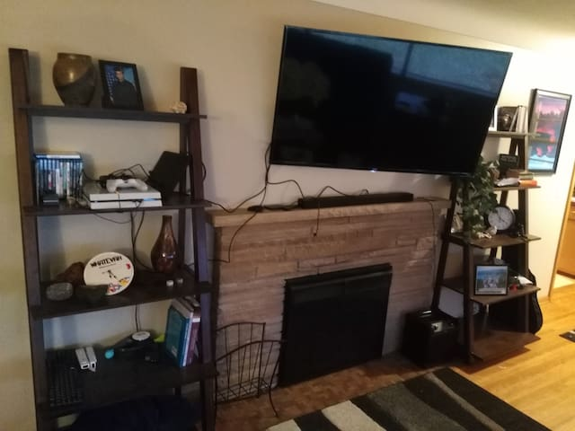 """55"""" 4k Roku TV with electric fireplace in living room. 2 large four person couches in living room that could sleep individuals if needed (pillows and blankets provided to make that possible)"""